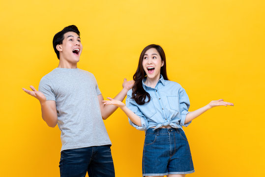 Excited young couple in casual clothing gesturing wow