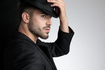 polite smart casual man holding black hat in studio