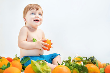Laughing blue-eyed baby sits in oranges on a light background.