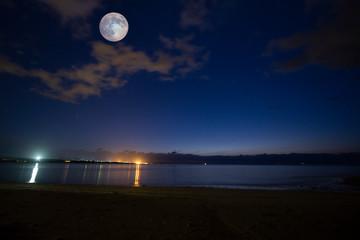 満月が穏やかな海と浜辺を照らす