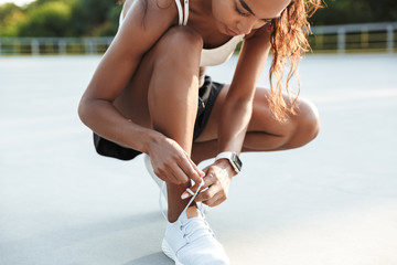Photo of beautiful focused woman tying shoelaces while working out