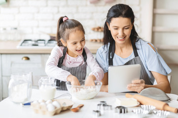 Mother and daughter using digital tablet in kitchen, looking recipe