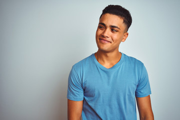 Young brazilian man wearing blue t-shirt standing over isolated white background smiling looking to the side and staring away thinking.