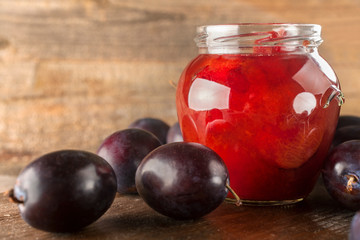 Preservation of freshly picked plums on a rustic wooden background