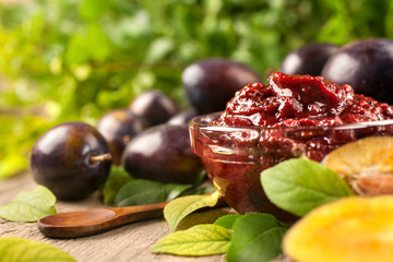 Jam of healthy organically grown plums with plum fruits on a wooden table background