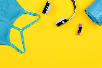 Layout of sport clothes and fitness accessories for women with fruits on yellow background.