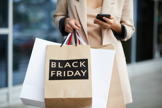 Mid-section portrait of stylish young woman holding shopping bags with Black Friday and texting on the go while leaving mall in sale season, copy space