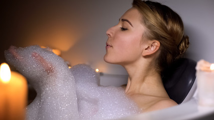 Cute woman in bath blowing bubbles, having fun, evening relaxation with candles
