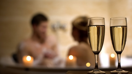 Glasses of champagne on foreground, lovers having pleasure pastime in bathroom