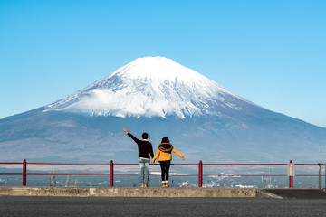 A happy Asian couple hold hand each other looking at big Mount Fuji from the hill. Concept of Japan travel with copy space on top.