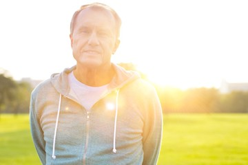 Active senior man standing in park with yellow lens flare in background