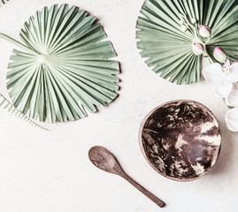 Wall Mural - Empty coconut bowl with spoon on white desk background with tropical leaves, top view. Copy space for your design or product