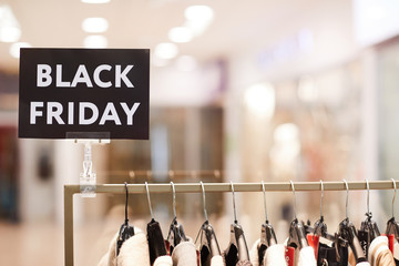Background image of BLACK FRIDAY sigh on rack with clothes on sale in shopping mall, copy space