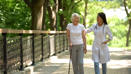 Doctor walking in park with elderly female patient with cane, rehabilitation