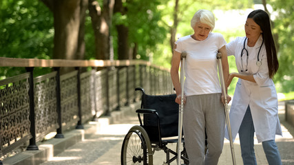 Doctor helping disabled old woman walking with crutches, recovery after trauma
