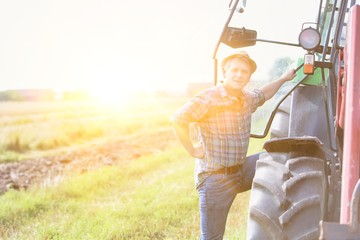 Mature farmer hopping to drive tractor in field with yellow lens flare in background