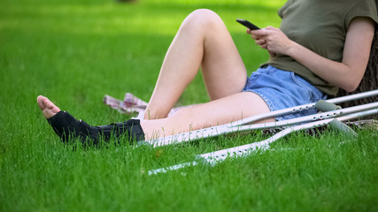 Woman in ankle brace sitting park with crutches scrolling smartphone, fracture