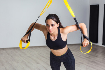 Portrait of young beautiful fit woman in black sportswear training arms with trx fitness straps in the gym doing push ups train upper body chest shoulders pecs triceps. Indoor, white wall background
