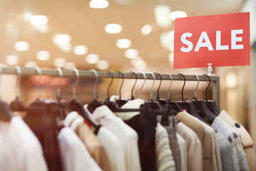 Background image of red SALE sigh on rack with clothes on display in shopping mall, copy space