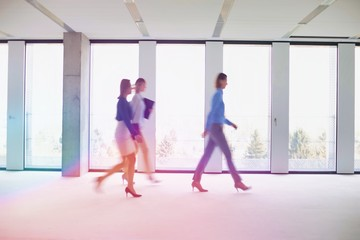 Business people walking in office corridor