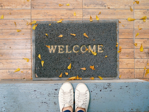 Top view selfie of feet in white sneakers shoes on floor background with welcome mat
