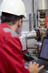 Digital control of the heating system. A technician dressed in red overalls and a white helmet check the heating parameters on laptop. Supervisory Control And Data Acquisition system in heating.