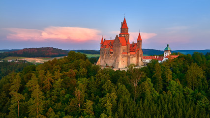 Aerial view on a romantic fairytale castle on a knoll in highland landscape, surrounded by trees. Gothic castle with high towers, red roofs, stone walls. Bouzov castle, Moravian region, Czechia.