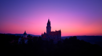 Aerial view on a silhouette of romantic fairytale castle in picturesque highland landscape, against pink and violet evening sky. Castle Bouzov with many towers, Moravia landscape, Czech republic.