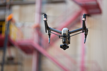 Hovering powerful black quadcopter with camera against blurred industrial construction. Visual inspection of hard to reach objects from the air in the industry. Front view.