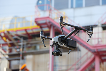 Hovering  black quadcopter with raised landing gears and powerful camera against blurred industrial construction. Visual inspection of hard to reach objects from the air in the industry. Side view.