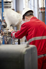 Energy industry. A technician dressed in red overalls and a white helmet checking the heating parameters. Heating water distribution technology. Service work in the power industry.