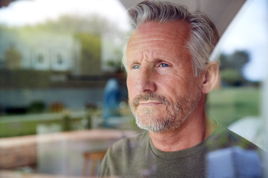 Senior Man Standing And Looking Out Of Kitchen Door Viewed Through Window