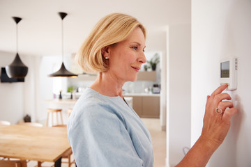Close Up Of Mature Woman Adjusting Central Heating Temperature At Home On Thermostat Wall mural