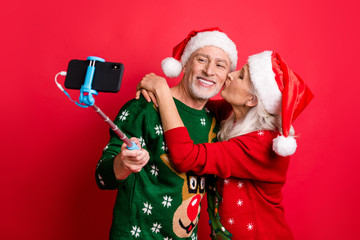 Blogging time social media concept. Photo of two romantic dreamy grey white haired sweethearts people married spouses making picture on cell using monopod hugging kissing in cheek isolated background
