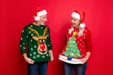 December you are crazy concept. Two excited cheerful positive nice glad friends husband wife people showing each other funky motley comic pictures of reindeer on jumpers isolated color background