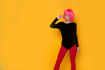 Pretty 90's style woman in a black body and red tights holding candy standing at the yellow wall