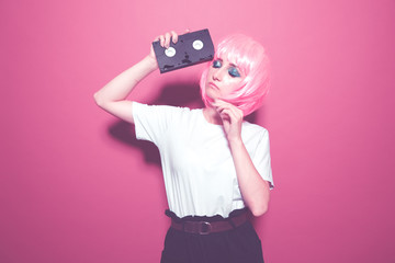 Retro girl in pink wig holding black cassette on the bright background Wall mural