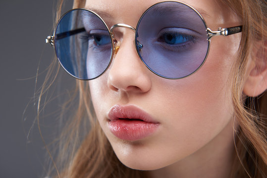 Beautiful teen girl with rosy full lips wearing blue round glasses