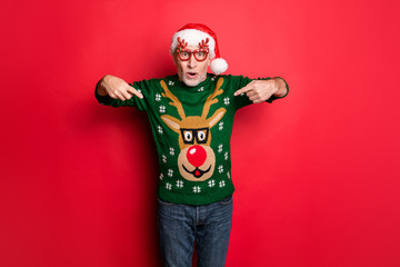 Did you see this. Photo of cheerful excited bearded grey-haired guy showing rudolf with red nose on his funky style december green retro knitted jumper pullover isolated bright color background