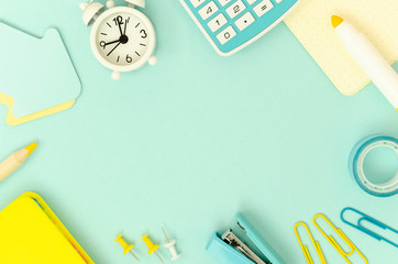 Flat lay frame school stationery, calculator and white alarm clock on a light blue background. Copy space for text. Back to school concept