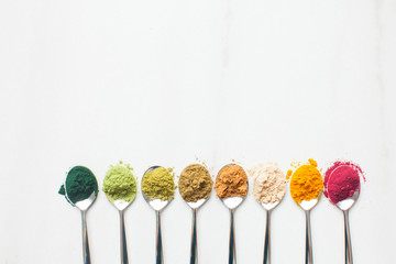 Kitchenware with different colorful superfood powders on wooden table