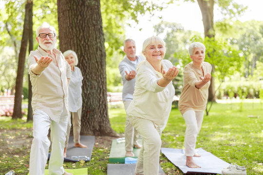 Smiling old people practicing qigong in the park