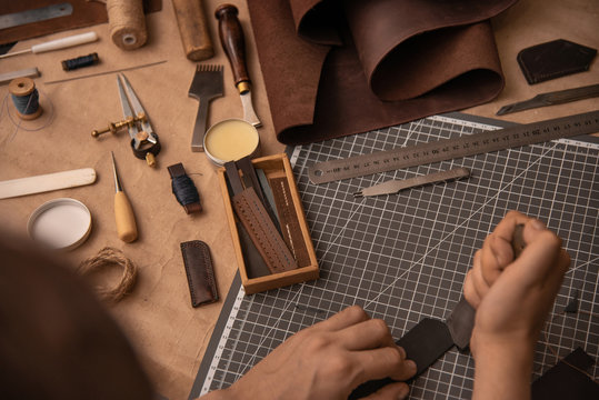 Working process in the leather workshop. Man's hands holding crafting tool