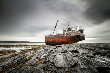 Abandoned ship on the coast of the Arctic Ocean.
