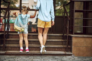 Mother and daughter returning home after shopping stock photo
