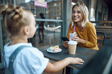 Woman with smartphone smiling to daughter stock photo