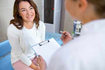 Cheerful woman talking with doctor in office stock photo