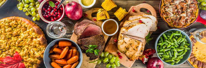 Thanksgiving family dinner setting concept. Traditional Thanksgiving day food  with turkey, green beans and mashed potatoes, stuffing, pumpkin, apple and pecan pies, rustic wooden table