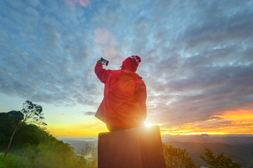 traveller woman enjoy takes picture the sunrise on the peak of mountain