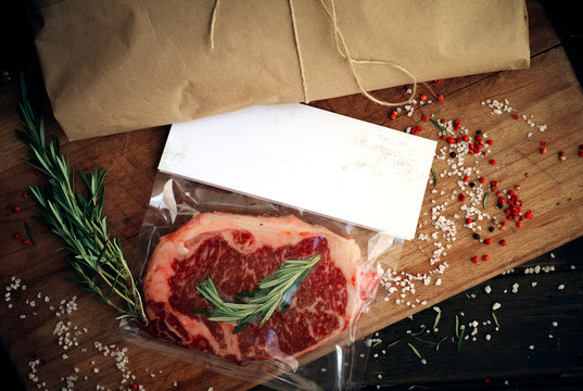 Raw beef steak vacuum Packed on wooden table, mockup for butcher shop or logo